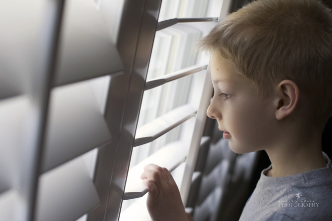 Boy looking out PolyWood Shutter Window