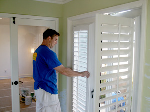 Installer installing shutters on French Door turning handle